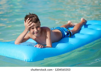 The portrait of cute European boy. He is laying on the blue inflatable floater, enjoying his holidays and smiling to the camera.