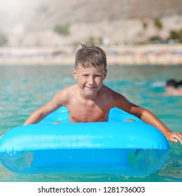 The portrait of cute European boy. He is sitting on the blue inflatable floater, enjoying his holidays and smiling to the camera.