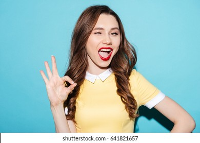 Portrait of a cute excited girl in dress showing ok gesture and winking isolated over blue background