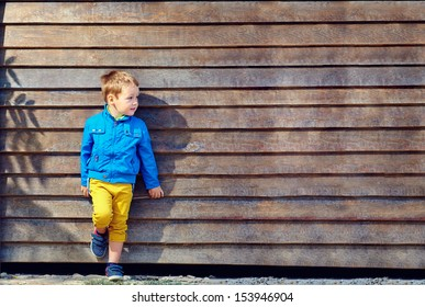 portrait of cute fashionable boy in front of wooden wall
