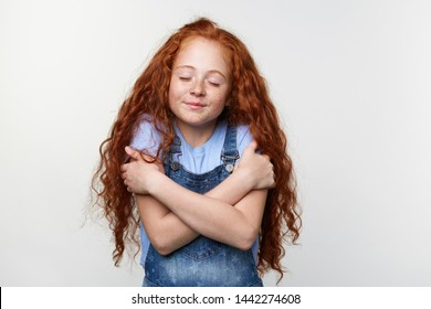 Portrait of cute freckles little girl with ginger hair, hugs himself and dreaming about puppy with closed eyes, stands over white background and dreamily smiling.