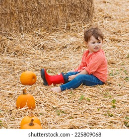 Portrait of a cute funny adorable  Caucasian baby toddler in red shirt and blue jeans sitting on hay on farm with pumpkins and trying to put on her red rain boots. Halloween Thanksgiving card