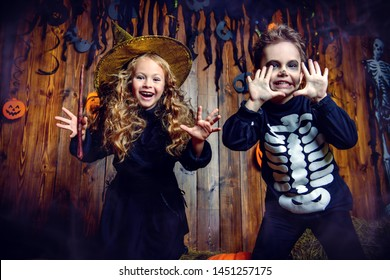 Portrait of a cute funny kids posing with pumpkins on a hay. Happy Halloween!
