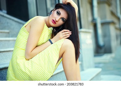 portrait of cute funny sexy young stylish smiling woman girl model in bright modern yellow dress with perfect sunbathed body outdoors in the city