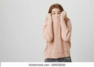 Portrait of a cute ginger girl hiding a face in a pull-up and looking with lifted eyebrows at camera, standing against a gray background. Teenager has pimple on chin and do not want to be photographed