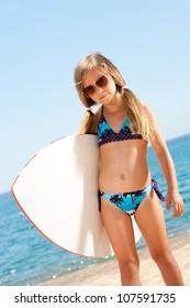 Portrait of cute girl in bikini holding white surfboard on beach.