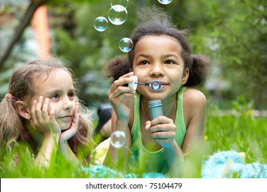 Portrait of cute girl blowing soap bubbles with her friend near by