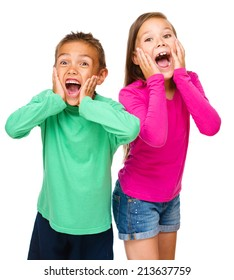 Portrait of cute girl and boy holding their faces in astonishment, isolated over white