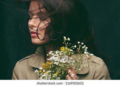 Portrait of a cute girl with a bunch of wild flowers.