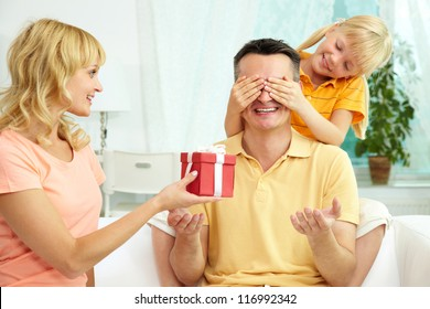 Portrait of cute girl closing male eyes by hands and happy woman holding gift for him