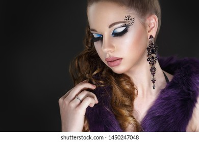 Portrait of a cute girl with a creative evening makeup on a black background.