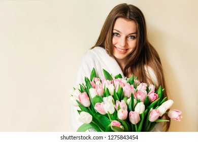 Portrait of a cute girl with a delicate bouquet of tulips.