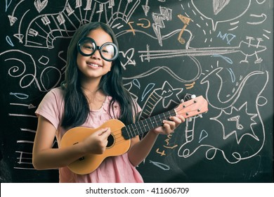 Portrait of cute girl in eyeglasses playing guitar by the blackboard with chalk drawings of musical instruments.