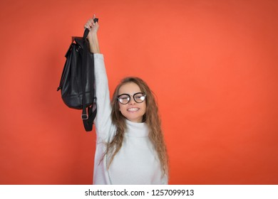 portrait of a cute girl with glasses on a red background and a bag in his hands