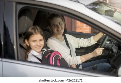 Portrait of cute girl going to school with mother by car