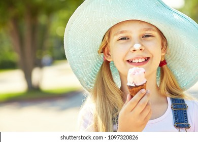 Portrait of a cute girl in hat with ice cream in a park. child outdoors