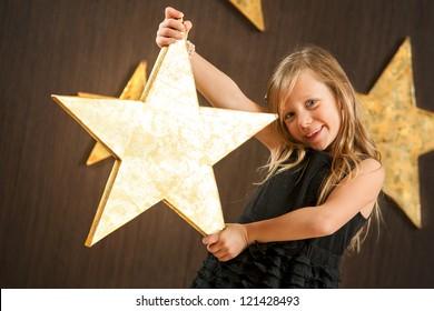 Portrait of cute girl holding big golden star.