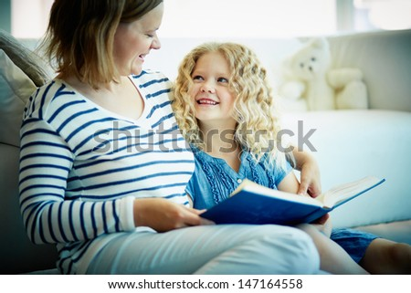 Portrait of cute girl listening to her mother telling an interesting story at home