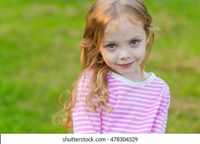 Portrait of a cute girl with long blond hair on nature