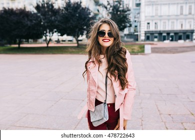 Portrait of cute girl with long curly hair and phone in hands smiling to camera in city on bulding background.