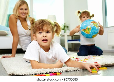 Portrait of cute girl looking at camera with her mother and twin sister on background