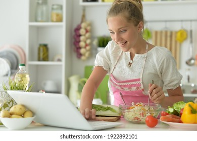 Portrait of cute girl making salad on kitchen and using laptop
