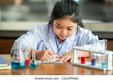 Portrait of cute girl posing with variety of reagents and writing result the test in school laboratory.