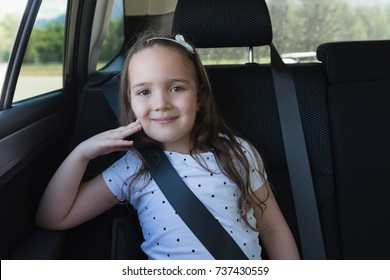 Portrait of cute girl sitting in back seat of car