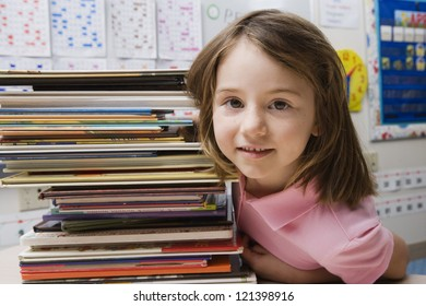 Portrait of a cute girl sitting with stack of books