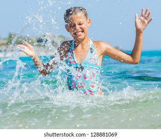 Portrait of cute girl swimming and squirting in the transparent sea