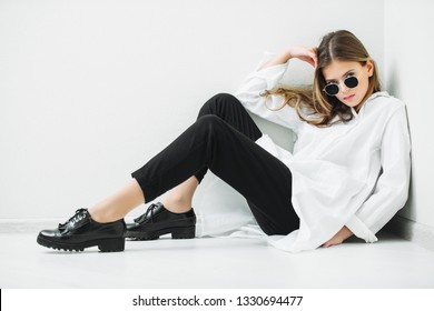 Portrait of a cute girl teenager with sunglasses sitting on the floor in the room. Glasses for a modern young generation. Beauty, fashion.