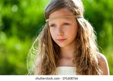 Portrait of cute girl wearing ribbon headband in green outdoors.