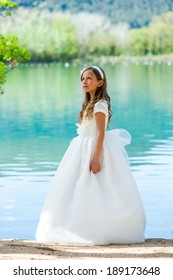 Portrait of cute girl in white dress standing at riverside.