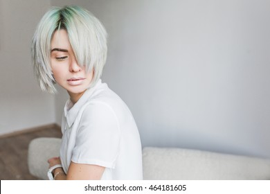 Portrait of cute  girl with white short  hairstyle  sitting on sofa in studio. She wears white dress. Her hair cover half  face. She is looking down.