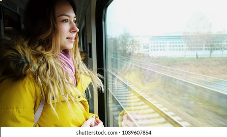 Portrait of cute girl who watches over  view from  window on  train and looks forward to getting off  transport at  station. European-looking girl with long blond hair smiles and looks at  camer