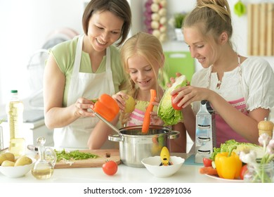 Portrait of cute girls with mother cooking in kitchen