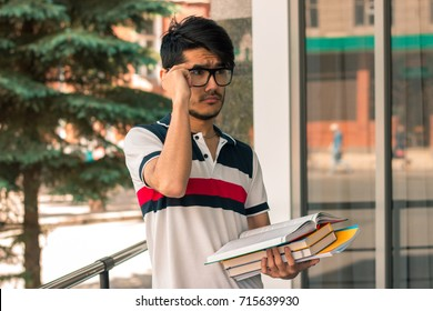 Portrait of a cute glamorous student in glasses with books