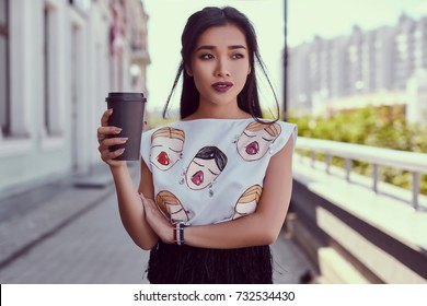 Portrait of a cute and gorgeous asian woman in fashion dress walking along bright european street with cup of coffee