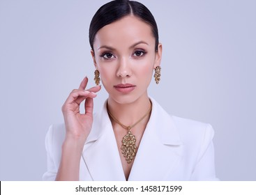 Portrait of a cute and gorgeous latin women in fashion white suit wearing expensive jewelry posing on bright studio background