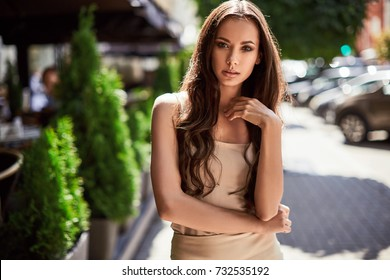 Portrait of a cute and gorgeous latin women in fashion dress posing and smiling along bright european street