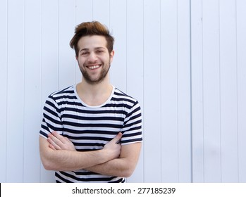 Portrait of a cute guy smiling with arms crossed on white background