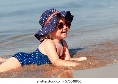 Portrait of cute happy baby girl in hat and sunglasses