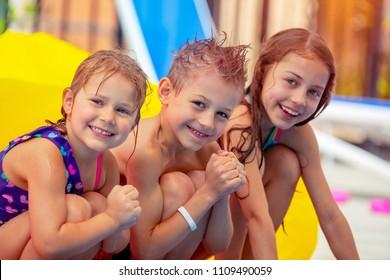 Portrait of a cute happy children having fun in aqua park, joyful siblings with pleasure spending summer holidays on the beach resort