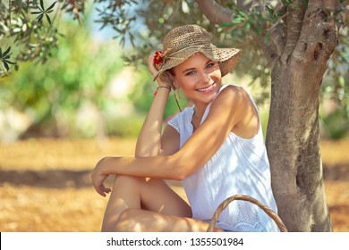 Portrait of a cute happy girl enjoying spring sunny day in the olive garden, resting in the shade of a tree with a picnic basket, weekend in countryside