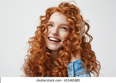 Portrait of cute happy girl smiling touching her curly red hair over white background.