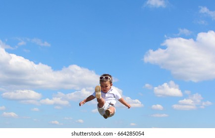 Portrait of cute happy kid small boy in the sky. Child having fun and enjoying sun in the panorama park. concept of flight. Trampolining.
