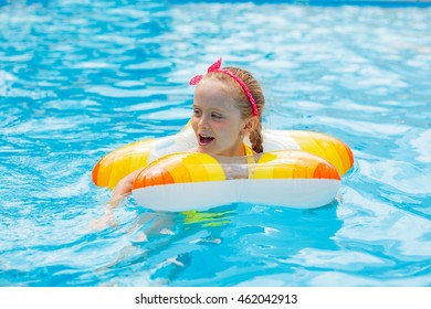 Portrait of cute happy little girl having fun in swimming pool, floating in blue refreshing water with big rubber ring, active summer vacation on the beach