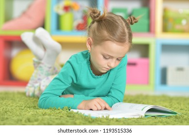 Portrait of cute happy schoolgirl studying at home