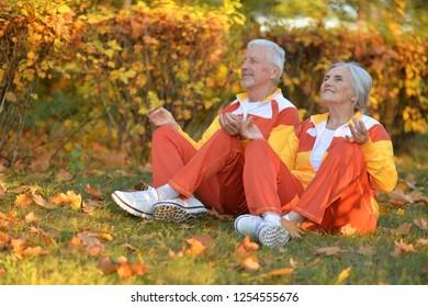 Portrait of cute happy senior couple meditating