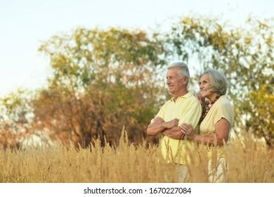 Portrait of cute happy senior couple in field